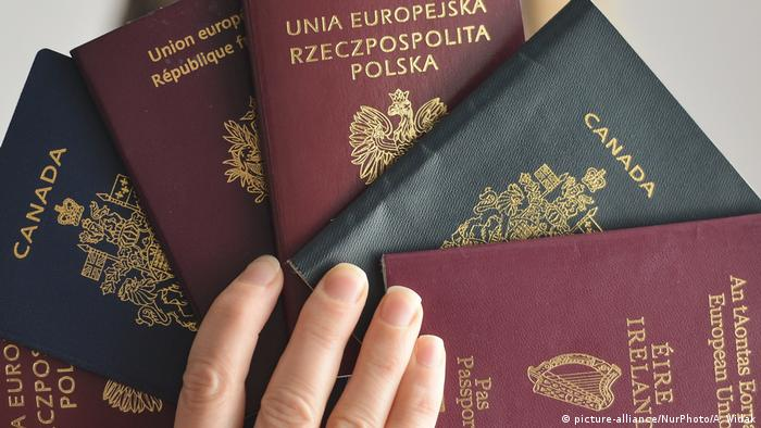 A hand holding up passports from different countries