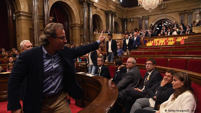 Representatives in the Catalan parliament watch an opposition lawmaker leave