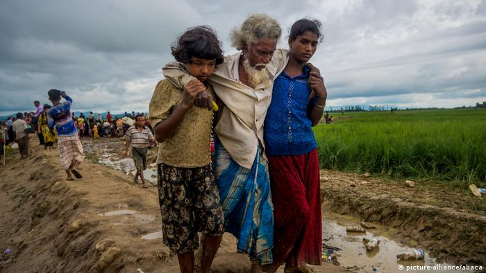 A Rohingya man fleeing from military operations in Myanmar is carried by two girls as they try to cross the border into Bangladesh