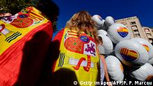 Two women wrapped with Spanish flags stand next to balloons bearing a heart-shaped collage of the Spanish, Catalan Senyera and EU flags as people begin to gather ahead of a pro-unity demonstration in Barcelona on October 29, 2017. Pro-unity protesters were to gather in Catalonia's capital Barcelona, two days after lawmakers voted to split the wealthy region from Spain, plunging the country into an unprecedented political crisis. / AFP PHOTO / PIERRE-PHILIPPE MARCOU (Photo credit should read PIERRE-PHILIPPE MARCOU/AFP/Getty Images)