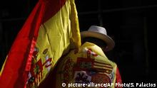A man wearing a Spanish flag walks along a street ahead of a rally against Catalonia's declaration of independence, in Barcelona, Spain, Sunday, Oct. 29, 2017. Thousands of opponents of independence for Catalonia held the rally on one of the city's main avenues after one of the country's most tumultuous days in decades. (AP Photo/Santi Palacios) |