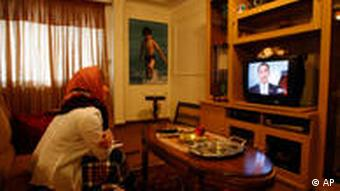 Iranian woman Marzieh Masaebi watches a TV video showing US President Barack Obama's new video message addressed to the Iranian people