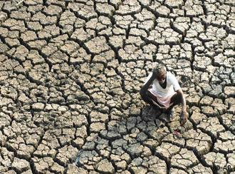 An Indian farmer on dried out ground