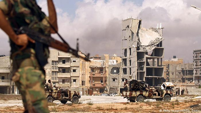 A soldier stands before two camoflaged cars patrolling a city with destroyed buildings in the background