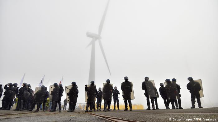 Riot police look up at the Floatgen wind turbine