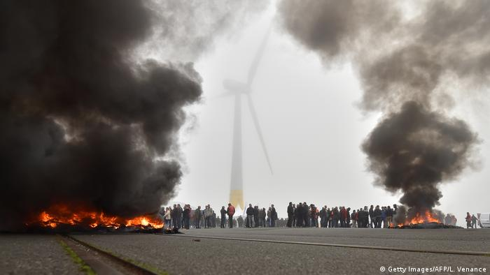 Smoke from burning tires rises into the air in front of a wind turbine