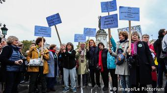 French protest against sexual harassment while waving signs