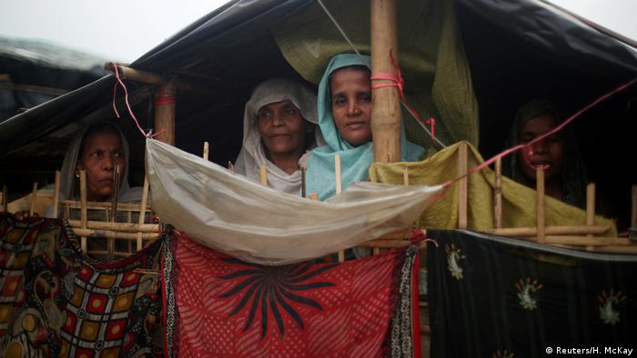 Rohingya women look out of a shelter in a refugee camp