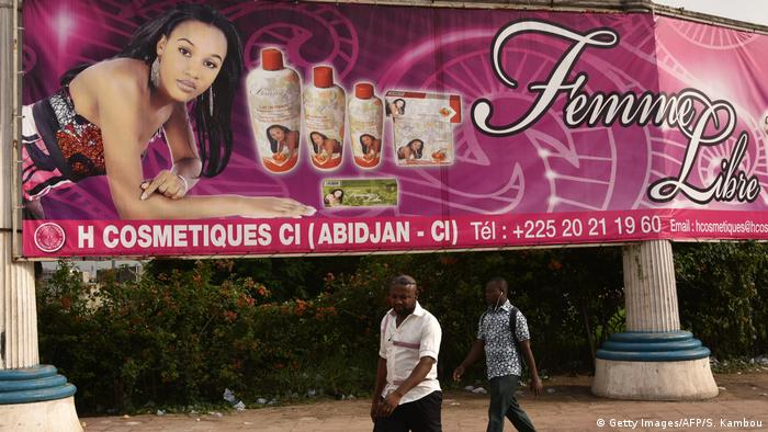 Two men walk under a large banner advertising cosmetics in Abidjan, Ivory Coast (Getty Images/AFP/S. Kambou)