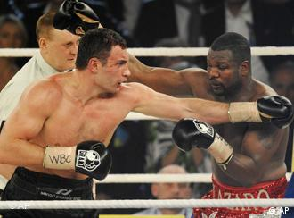 Ukrainian boxer Vitali Klitschko, left, punches Juan Carlos Gomez from Cuba, right, in a WBC heavyweight world championship fight in Stuttgart, Germany, late Saturday, March 21, 2009