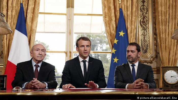 French President Emmnauel Macron, center, addresses the medias with French Interior Minister Gerard Collomb, left, and government spokesman Christophe Castaner after signing a counterterrorism law