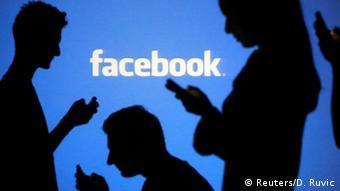 Люди со смартфонами в руках на фоне логотипа Facebook