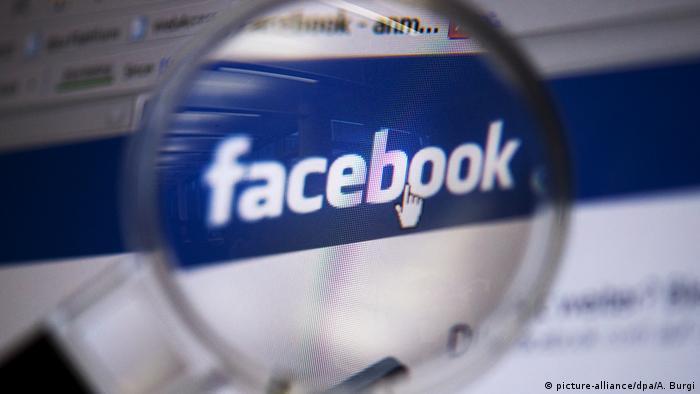 Facebook logo seen through a magnifying glass
