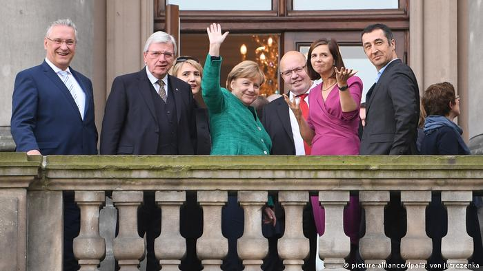 German politicians stand on a balcony and wave to those below (picture-alliance/dpa/B. von Jutrczenka)