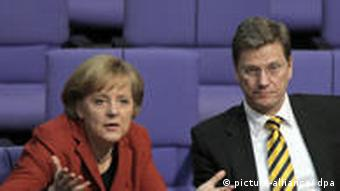Chancellor Angela Merkel (left) and Guido Westerwelle sit in parliament