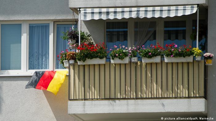Eine Deutschland-Fahne hängt während der Fußball-WM 2014 aus einem Fenster neben einem Balkon in Berlin-Friedrichshain (Foto: dpa)