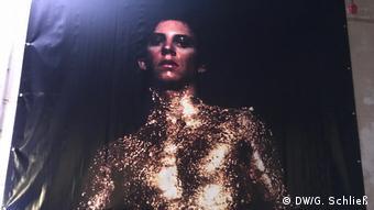Man sieht den Maler Luciano Castelli als jungen Mann in eng anliegenden goldenem Glitzeranzug