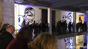 Man sieht Besucher an einer Balustrade stehen, dahinter große Wandmalereien von Gesichtern in Schwarz-Weiß