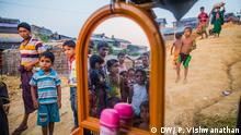 A mother and child stand along with displaced Rohingya refugees queuing up from 4:00 am in the morning for relief from World Food Programme in Kutupalong camp, in Cox's Bazar, Bangladesh, Sunday, Oct. 24 2017. Photographer: Prashanth Vishwanathan/ DW_Stories