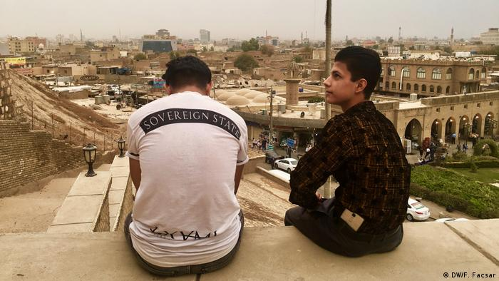 Two young men sit on a tall building looking out over Erbil, the capital of Iraqi Kurdistan. One man is wearing a T-shirt that says sovereign state in English.