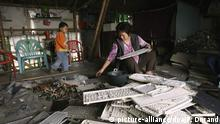 Chinese workers sort out vast quantities of obsolete electronics material shipped in from the United States, Europe and Japan and piled in mountains of waste in the city of Guiyu, Southern China on December 2006. Even as entire communities, including children, earn their livelihoods by scavenging metals, glass and plastic from the dumps, the technological garbage is poisoning the water and soil and raising serious health concerns. They are working in family. Foto: Patrick Durand +++(c) dpa - Report+++  