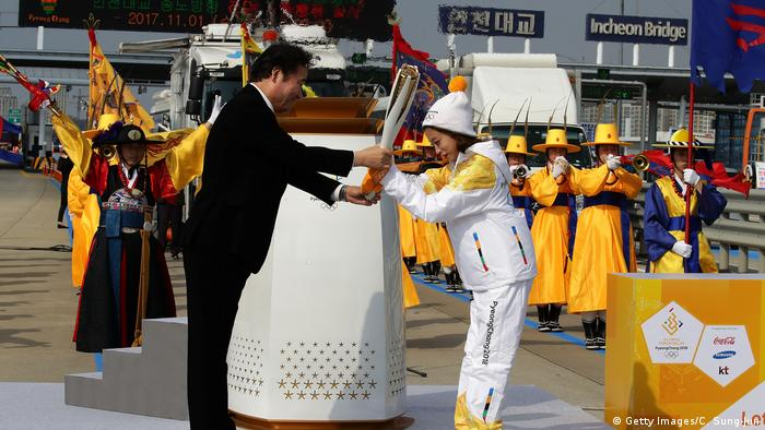 South Korean figure skater You Young receivesthe PyeongChang 2018 Winter Olympics torch from South Korean prime minister Lee Nak-yon