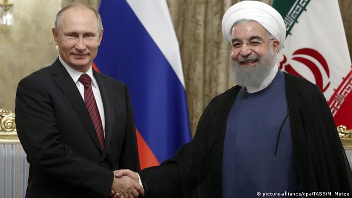 Russian President Vladimir Putin and Iranian President Hassan Rouhani shake hands at the beginning of the former's official visit to Iran