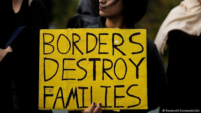 A protesters holds a sign that reads: Borders destroy families