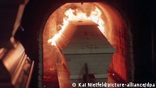 Ein Sarg wird in den Verbrennungsofen gefahren und fängt dort sofort Feuer. Links stehen weitere aufgestapelte Särge bereit. Der Trend geht zur Urne: Auch beim letzten Weg des Menschen - dem zum Friedhof - wird in Deutschland gespart. Immer mehr wollen verbrannt werden, denn die Urnenbestattung ist in der Regel um die Hälfte billiger als das Erdbegräbnis. Die Anzahl der Feuerbestattungen steigt stetig. Waren es 1995 noch 16261 Einäscherungen, sind bereits ein Jahr später 16750 Einäscherungen im Hamburger Krematorium vorgenommen worden. Dort werden am Tag im Drei-Schicht-System 72 Verbrennungen an vier Öfen durchgeführt Aufgenommen am 31. Januar 1997. | Verwendung weltweit