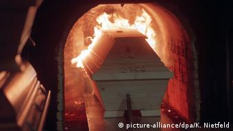 A coffin enters a cremation oven in the Hamburg cemetery (picture-alliance/dpa/K. Nietfeld)