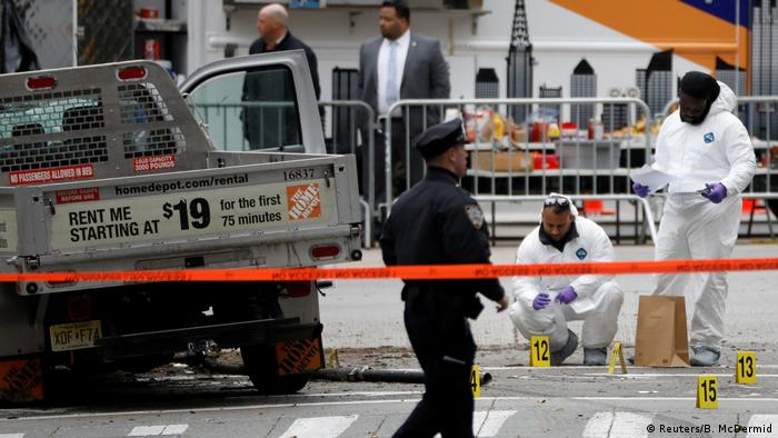 Police stand behind a tape on the investigation site of the New York Halloween terror attack