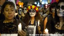 Women carry candles and pictures of murdered women during a Day of the Dead march calling for justice for victims of femicide, in front of the Metropolitan Cathedral, Mexico City, Wednesday, Nov. 1, 2017. Mothers of women who were murdered led the march by more than 100 women wearing traditional Catrina face paint and carrying pictures of women who have been killed. (AP Photo/Rebecca Blackwell) |