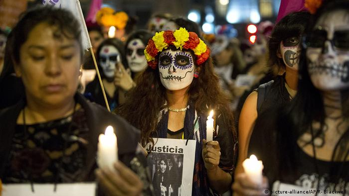 Women carrying candles protest femicide during a Day of the Dead march in Mexico City