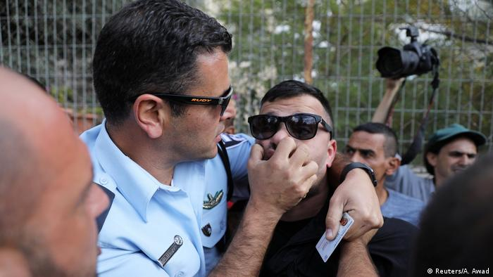 An Israeli policeman scuffles with a protester
