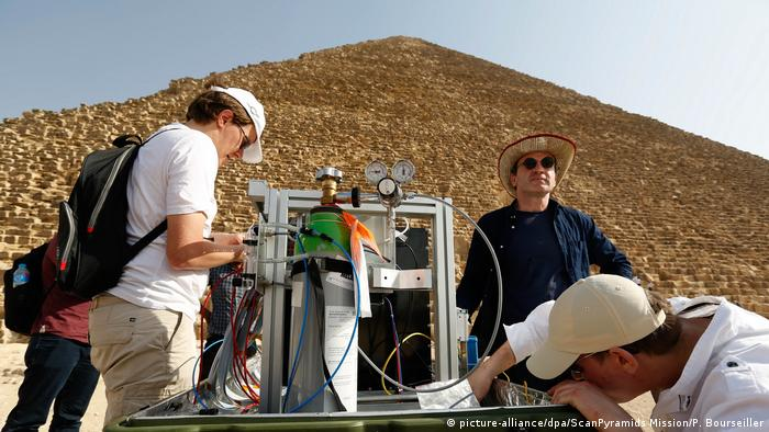 Scientists and a device positioned in front of a pyramid (picture-alliance/dpa/ScanPyramids Mission/P. Bourseiller)