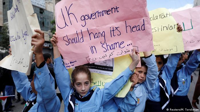 Child lifts up a banner reading UK gov't shuld hang its head in shame... (Reuters/M. Torokman)