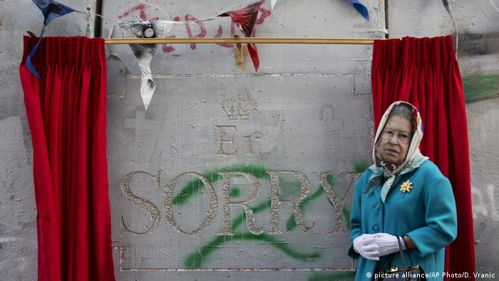 A woman wearing a mask of Queen Elisabeth stands next to the message by the elusive artist Banksy