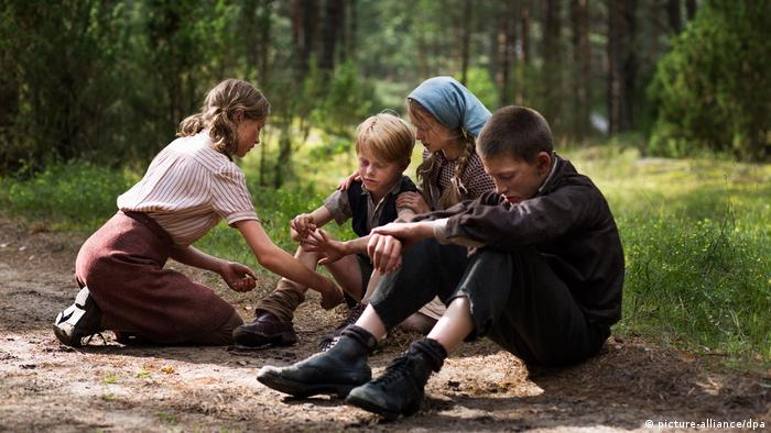 Children sit in the woods in scene from the 2012 movie Wolfskinder