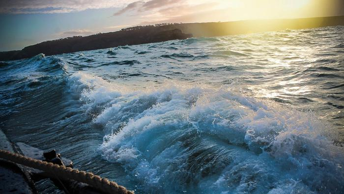 Waves crashing against a boat at sunset