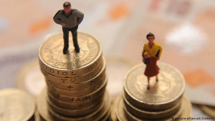 Male and female figurines standing on piles of pound coins (picture-alliance/J.Giddens)