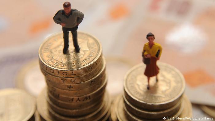 Bonecos de homem e de mulher sobre pilhas de moedas