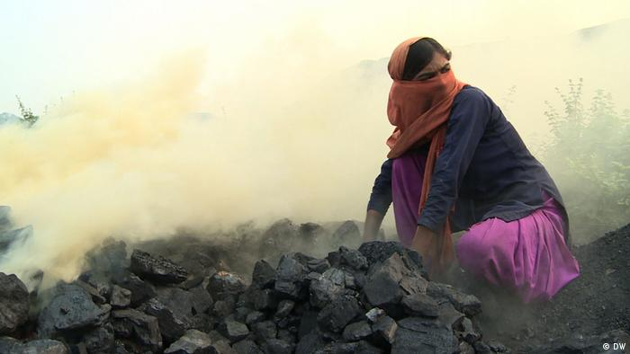 A woman with a scarf around her mouth as fumes fill the air. In front of her is a pile of coal