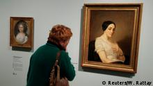 A woman looks at an oil painting entitled Portrait of a Young Woman by French artist Thomas Couture (1815-1879), which is identified as a Nazi-looted art during a media preview of the Gurlitt: Status Report - Nazi Art Theft and its Consequences exhibition at the Bundeskunsthalle in Bonn, Germany, November 2, 2017. REUTERS/Wolfgang Rattay NO RESALES. NO ARCHIVE