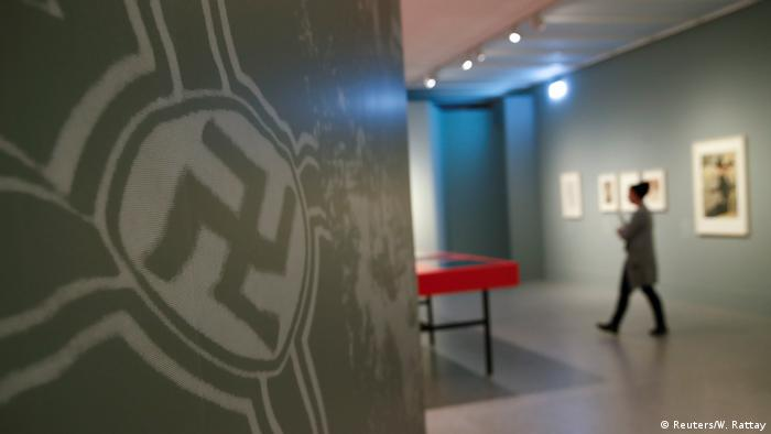 A woman walks past a Swastika during a media preview of the Gurlitt: Status Report - Nazi Art Theft and its Consequences