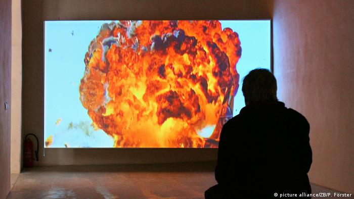Still from Hito Steyerl's video installation 'After the Crash': A person watching an explosion on screen