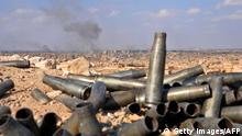 Spent artillery shells lie in a heap as smoke billows in the background, in Deir el-Zour.