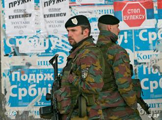 Belgium KFOR peacekeepers patrol past a posters reading Support Serbia, Stop Eulex, EU mission in Kosovo and We want Russian army, in northern, Serb-dominated part of ethnically divided town of Kosovska Mitrovica, Kosovo