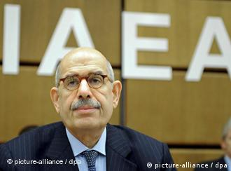 Mohamed ElBaradei sits in front of an IAEA sign
