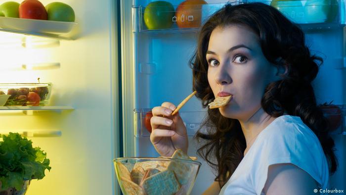 Djevojka jede pred otvorenim hladnjakom (Colourbox)