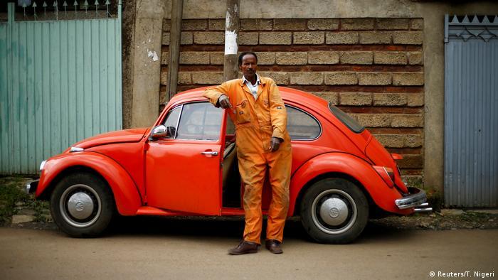 Механик в Аддис-Абебе стоит рядом со старым автомобилем VW Käfer